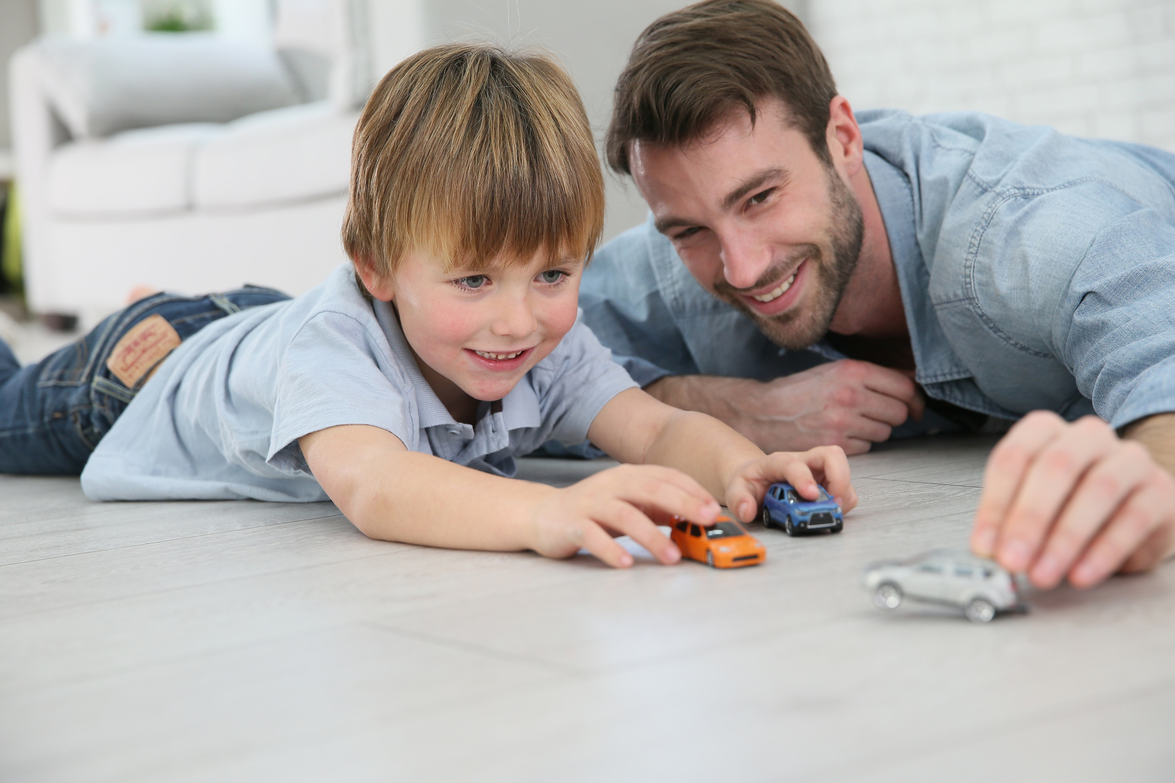 Dad And Son Playing With Toy Cars